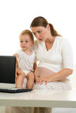 Pregnant mom and child with laptop Royalty Free Stock Image