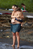 A pregnant mom hugging her grown child  on the black beach Stock Photo