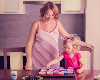Pregnant mom with little daughter preparing cupcakes. Royalty Free Stock Photos