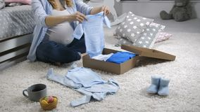 Pregnant mom opening baby clothes gift box. Midsection of pregnant woman opening paper gift parcel with baby clothes for newborn boy. Female unpacking the box stock footage