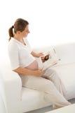 Pregnant mom reading on sofa Royalty Free Stock Image