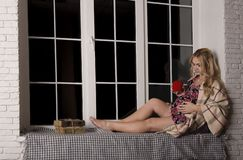 Pregnant mom is resting on the windowsill. with a cup of warm te royalty free stock image
