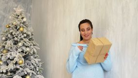Pregnant mom stands by the Christmas tree with White Christmas gifts stock video