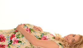 Pregnant mom. Young blonde pregnant woman in floral print dress laying down and smiling royalty free stock photos
