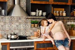 Pregnant mother and blonde little daughter talking at home in the kitchen royalty free stock images