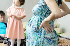 Pregnant mother with children on background, pregnancy belly of woman. Happy motherhood. Expecting baby birth in third trimester. Being mother. Prenatal period Stock Photos