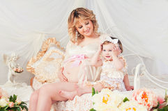 Pregnant mother and cute little daughter in cozy room with flowers Stock Photos