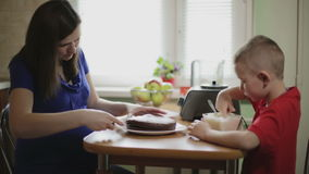 A pregnant mother cutting a cake, her son eating cream. stock footage