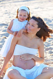 Pregnant mother and daughter on the beach royalty free stock photos