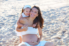 Pregnant mother and daughter on the beach royalty free stock images