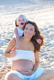 Pregnant mother and daughter on the beach stock photos