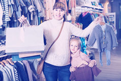 Pregnant mother and daughter choosing romper suit for baby in ch Royalty Free Stock Photo