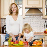 Pregnant mother and daughter in kitchen Stock Images
