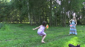 Pregnant mother with daughter play badminton. Left side slide stock video footage
