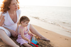 Pregnant mother and daughter playing in beach sand. Of Mediterranean royalty free stock photos