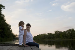 Pregnant Mother And Daughter Sitting On Jetty Stock Photo