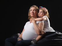 Pregnant mother and daughter together Stock Photo