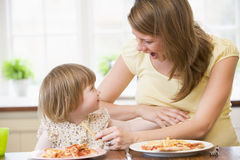Pregnant mother with daughter touching belly Stock Photo