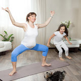 Pregnant mother doing fun yoga training with her kid girl and pe Stock Photo