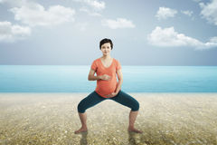 Pregnant mother doing yoga at the beach Stock Photos