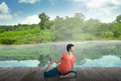 Pregnant mother doing yoga at the lake Stock Images