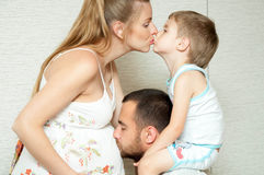 Pregnant mother, father and son are kissing. Happy familly wait new baby Stock Image