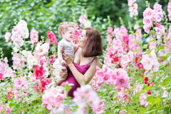 Pregnant mother with her baby daughter in flowers Royalty Free Stock Photography