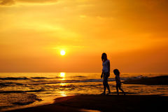 Pregnant mother and her child as silhouettes. By the sea royalty free stock photos