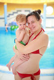 Pregnant mother with her child in swimming-pool. Pregnant mother with her lovely child in swimming-pool Royalty Free Stock Photography