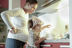 Pregnant mother and her daughter cooking in the kitchen Stock Photos