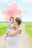 Pregnant mother and her daughter Stock Images