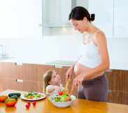 Pregnant mother with her daughter at kitchen Royalty Free Stock Photos