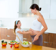 Pregnant mother with her daughter at kitchen. Beautiful pregnant mother with her daughter at kitchen preparing salad stock image
