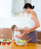 Pregnant mother with her daughter at kitchen Royalty Free Stock Photography