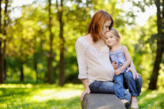 Pregnant mother with her daughter outdoors Stock Photo