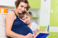 Pregnant mother with her daughter reading book Stock Images
