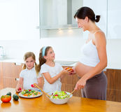 Pregnant mother with her daughters at kitchen. Beautiful pregnant mother with her daughters at kitchen preparing salad Stock Image