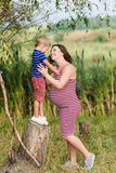 Pregnant mother and her son playing together Stock Images