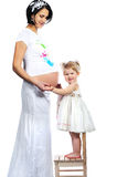 Pregnant mother with her sweet little baby girl isolated on whit Stock Images
