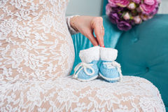 Pregnant mother holding little knit baby shoes Stock Photo