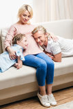 Pregnant mother hugging husband and daughter while resting on sofa at home Stock Image