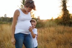 Pregnant mother hugging her son. A pregnant mother hugs her son by the shoulders. A family portrait outside the city. Happy childhood and motherhood Stock Photos