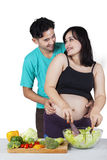 Pregnant mother and husband cooking salad Stock Photo