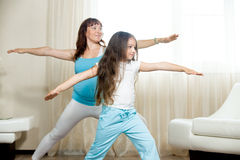 Pregnant mother and kid girl practicing yoga at home stock image