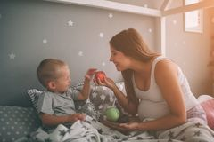 Pregnant mother and little boy son are eating an apple and peach in the bed t home in the morning. Casual lifestyle in royalty free stock photography