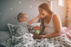 Pregnant mother and little boy son are eating an apple and peach in the bed t home in the morning. Casual lifestyle in royalty free stock images