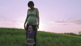 Pregnant mother and little daughter are dancing on a green meadow on a background of scarlet sunset. stock video footage