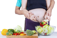 Pregnant mother making vegetables salad with husband Stock Photo