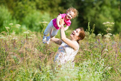 Pregnant mother playing with her toddler in meadow Royalty Free Stock Photos