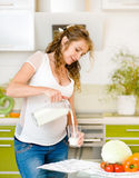 Pregnant mother pour out milk. Beautiful pregnant mother pour out milk into glass on the house Stock Photo